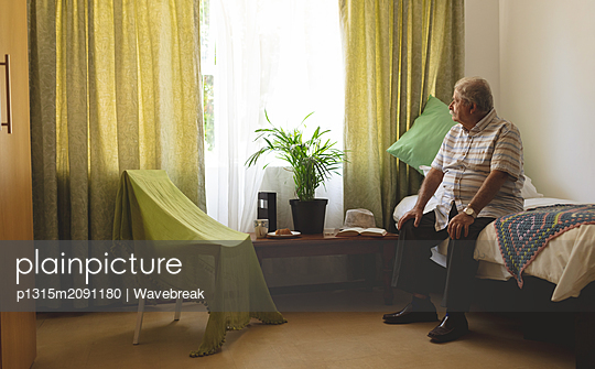Sad senior male patient looking outside the window on a nursing home bed - p1315m2091180 by Wavebreak