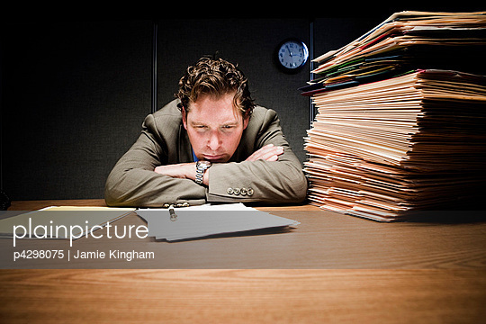 Stressed man with head down on desk - p4298075 by Jamie Kingham