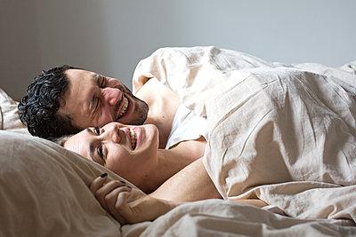 Junges Paar liegt nebeneinander im Bett und lacht  - p1301m1424743 von Delia Baum