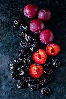 Fresh and dried plums  on dark ground - p300m1580710 by Dieter Heinemann