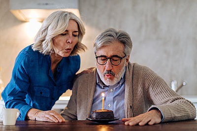 Mature couple celebrating birthday with cake in kitchen at home - p300m2160331 by Sofie Delauw
