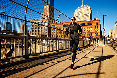 Woman jogging in city - p343m2046951 by Josh Campbell