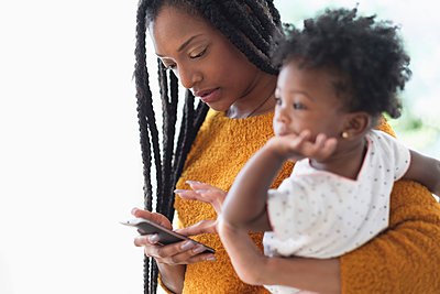 Black woman holding baby daughter using cell phone - p555m1305415 by JGI/Tom Grill