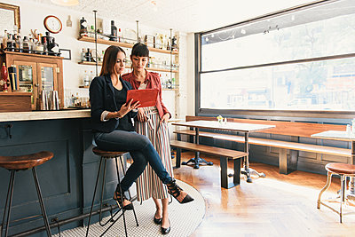 Two young women looking at digital tablet in cocktail bar - p924m1197135 by Matt Dutile