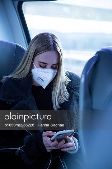 Junge Frau mit FFP2 Maske mit Smartphone im Zug - p1650m2285228 von Hanna Sachau