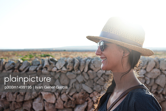 Spain, Menorca, happy single traveller wearing straw hat and sunglasses at backlight