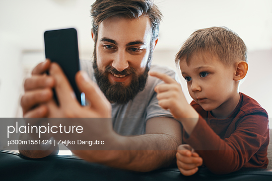 Portrait of father and little son with smartphone - p300m1581424 von Zeljko Dangubic
