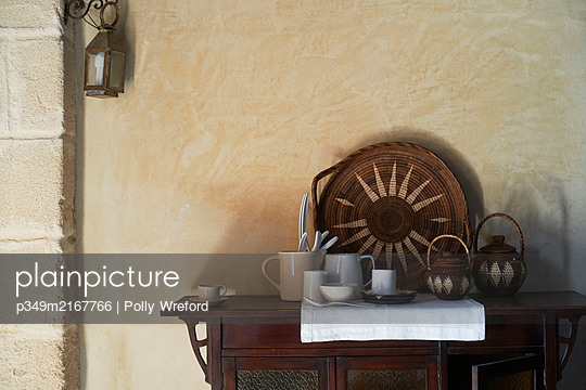 Sunburst tray and teapots with ceramics on wooden sideboard in Sicilian home - p349m2167766 by Polly Wreford