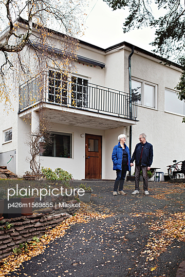 Full length of smiling retired senior couple standing against house - p426m1569855 by Maskot