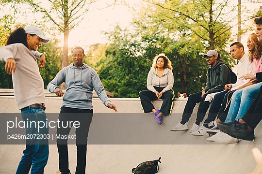 Friends looking at men dancing in skateboard park - p426m2072303 by Maskot