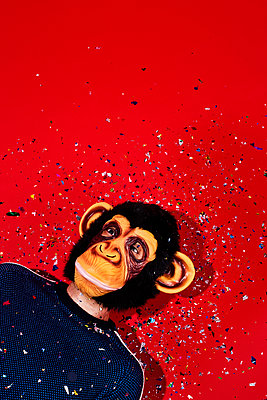 Man wearing a monkey mask on a red background - p1423m2164199 by JUAN MOYANO