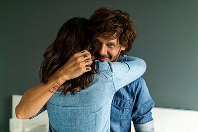 Smiling tattooed man embracing girlfriend - p300m2059652 von Valentina Barreto