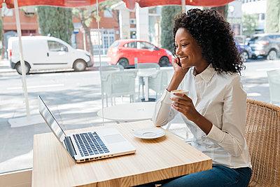 Business afro woman in coffee shop, Sevilla, Spain - p300m2300216 von Julio Rodriguez