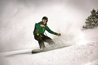 A snowboarder riding through powder.  - p343m1184695 by Rob Hammer