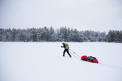 Mature woman pulling backpack on sled in snow - p426m1131033f by Katja Kircher