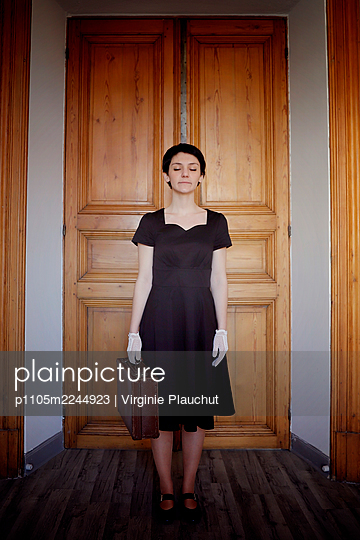 Woman in black dress and suitcase - p1105m2244923 by Virginie Plauchut