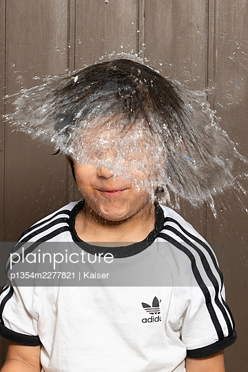 A water balloon bursting on a child's head - p1354m2277821 by Kaiser