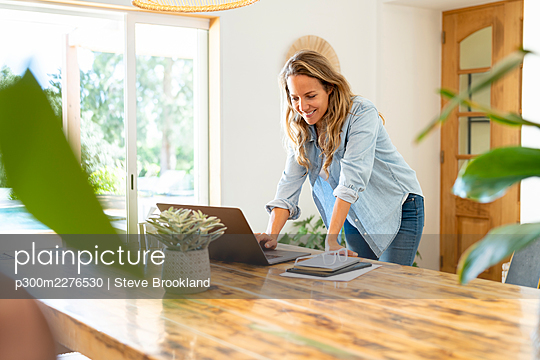 Smiling businesswoman using laptop while leaning on table at home - p300m2276530 by Steve Brookland