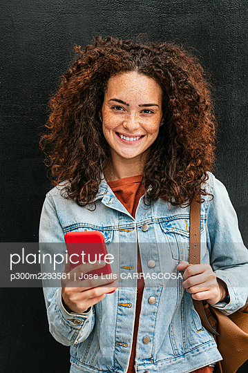 Beautiful young woman holding mobile phone - p300m2293561 by Jose Luis CARRASCOSA