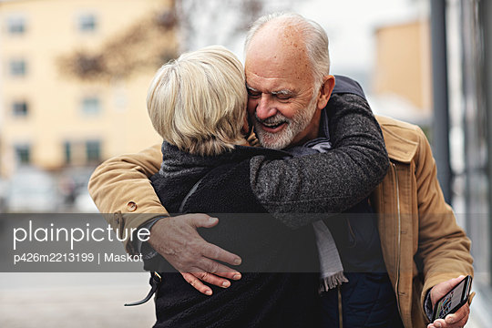 Smiling senior man embracing partner during winter in city - p426m2213199 by Maskot