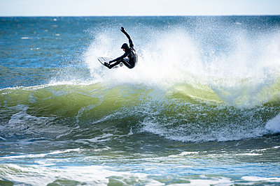 Surfer in mid-air above wave - p343m1585191 by Cate Brown