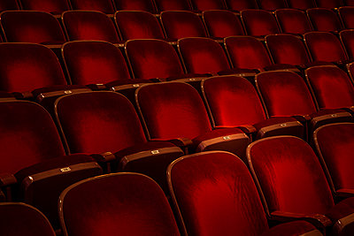 Rows of empty red chairs in a theater - p397m1573937 by Peter Glass