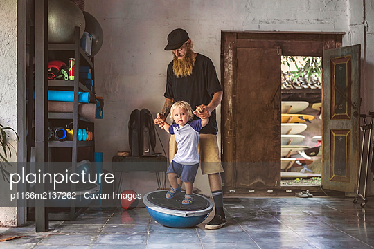 Father with little boy pling in gym - p1166m2137262 by Cavan Images