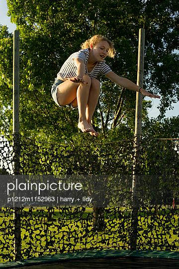Mädchen auf dem Trampolin - p1212m1152963 von harry + lidy