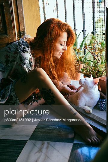 Red-haired tattooed woman playing with her cat at home - p300m2131992 by Javier Sánchez Mingorance