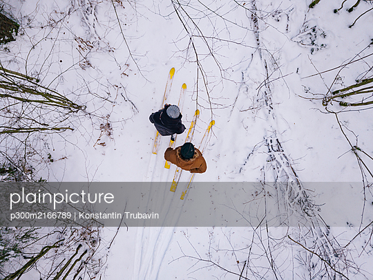 Aerial view of couple with skis in the forest, Leningrad region, Russia - p300m2166789 by Konstantin Trubavin