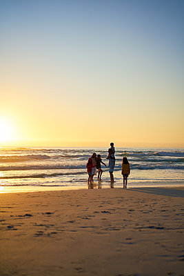 Family wading in ocean surf on beach at sunset - p1023m2200901 by Trevor Adeline