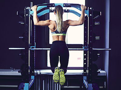 Rear profile of young woman doing chin ups at fitness centre - p1166m2095506 by Cavan Images