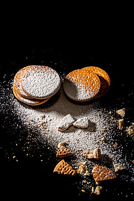 Artisan cookies piled on a black background with powdered sugar glass - p1166m2192025 by Cavan Images