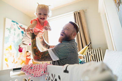 Father playfully lifting daughter over laundry basket - p1192m1158170 by Hero Images