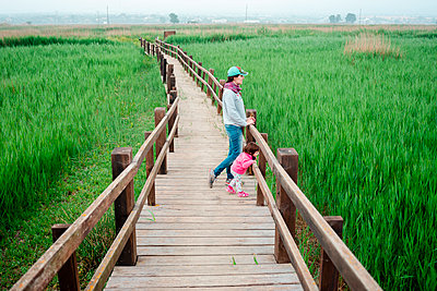 Mother and daughter on a wooden walkway, looking at rice fields - p300m2058818 by Gemma Ferrando