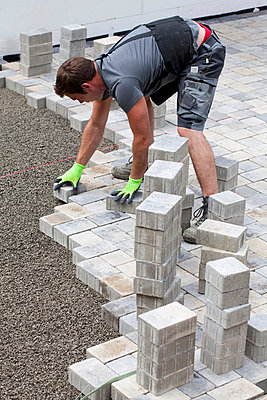 Young man assembling paving stones - p300m798169f by Dieter Heinemann