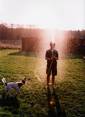 A boy spraying a garden hose - p3012780f by fStop