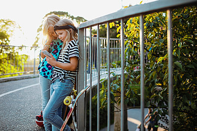 Friends using mobile phone while leaning on railing during sunny day - p426m1226384 by Maskot
