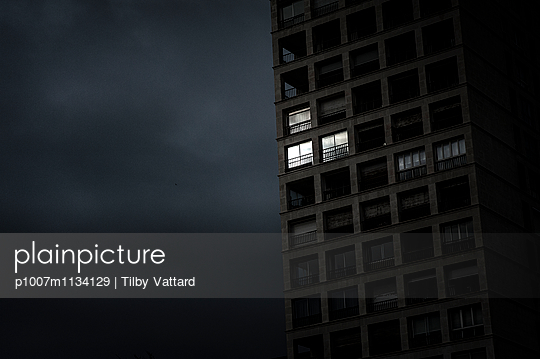 Sun reflected in the windows of a dark building - p1007m1134129 by Tilby Vattard