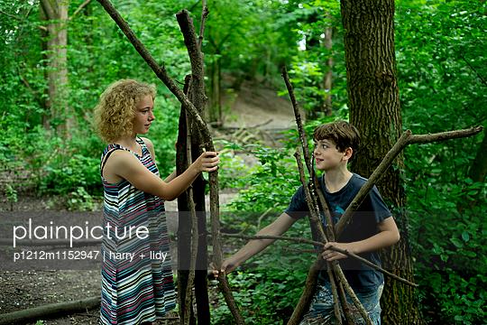Kinder bauen eine Hütte im Wald - p1212m1152947 von harry + lidy