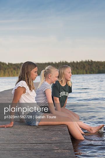 three girls on a jetty - p1323m1582728 von Sarah Toure