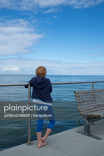 Boy looks out onto the sea - p236m2196629 by tranquillium