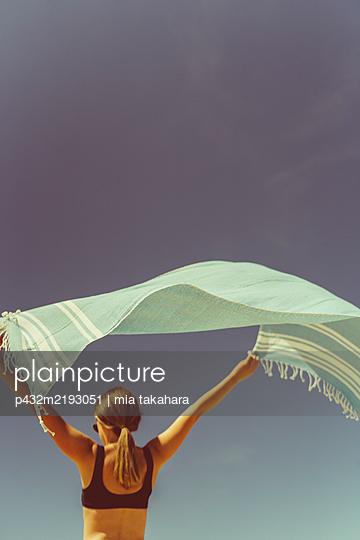 Junge Frau bewegt sich mit Strandtuch im Wind - p432m2193051 von mia takahara