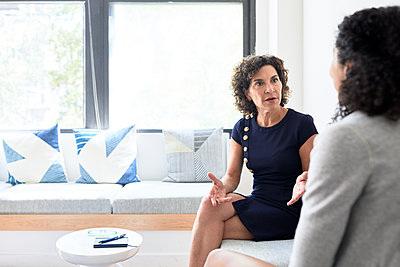 Senior businesswoman discussing with female colleague while sitting on sofa at creative office - p1166m1523269 by Cavan Images
