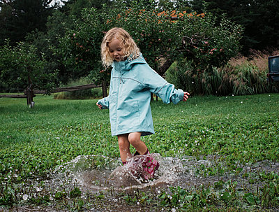 Playful girl splashing water in puddle at apple orchard - p1166m2024803 by Cavan Images
