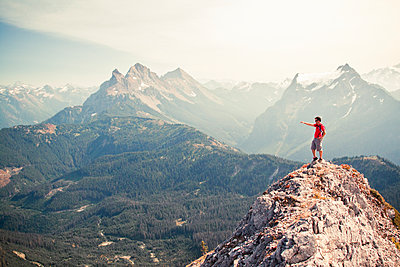 Hiker pointing across valley from rocky mountain summit - p1166m2269414 by Cavan Images