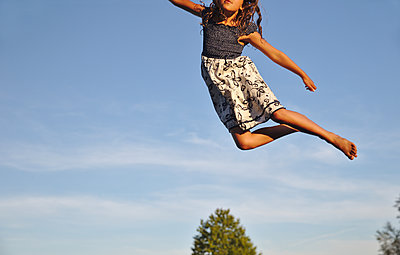 Girl jumping high into the sky - p1231m2211176 by Iris Loonen
