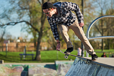 Young adult on skateboard dropping in on ramp, Montreal, Quebec, Canada - p1362m1553697 by Charles Knox