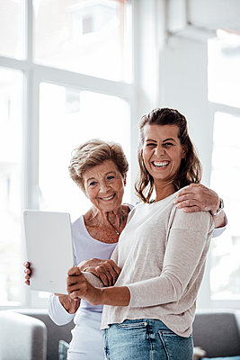 Cheerful young woman holding digital tablet by grandmother at home - p300m2276969 by Gustafsson