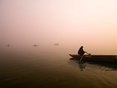Ganges River,Varanasi,India;Person rowing canoe on the river at sunset - p4429248 by Keith Levit